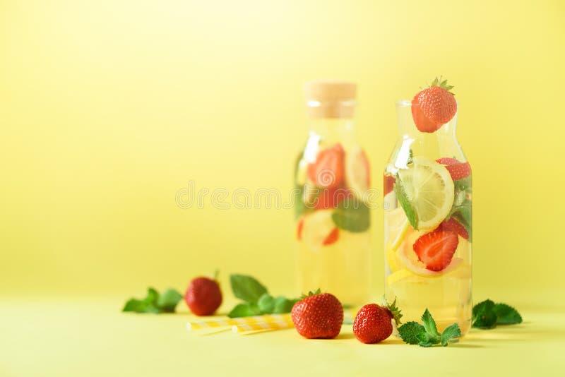草莓戒毒所水用薄菏,在黄色背景的柠檬 柑橘柠檬水 钞票 夏天果子被灌输的水 复制 免版税图库摄影