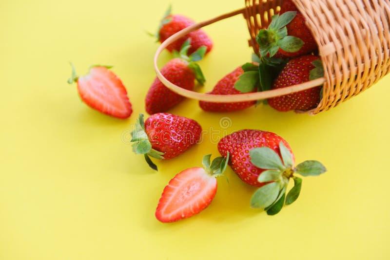 草莓新鲜在黄色背景-采摘在篮子的成熟红色草莓 免版税库存图片