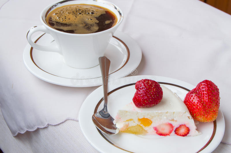草莓点心片断在白色板材和杯咖啡的 库存照片