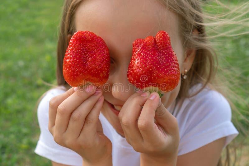 草莓眼睛 拿着在眼睛的美丽的少女草莓象双筒望远镜在庭院里 健康,生活方式概念 图库摄影