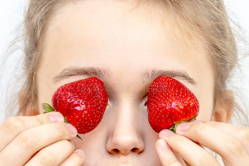 草莓眼睛 拿着在眼睛的美丽的年轻女人草莓象双筒望远镜 免版税库存照片