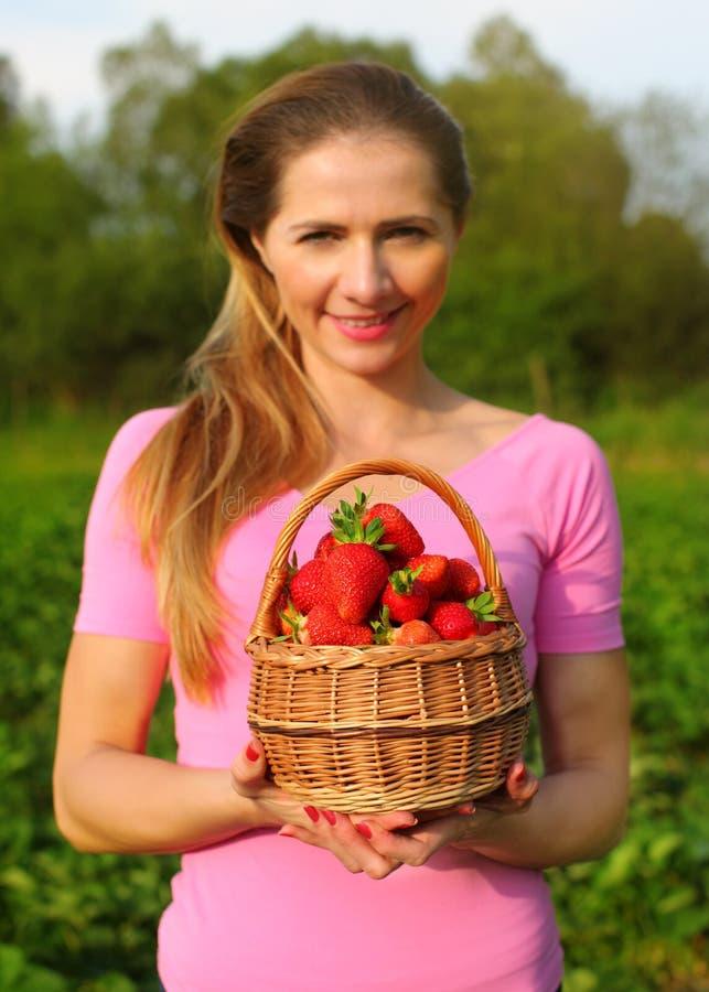 草莓篮子由少妇举行了在与s的焦点外面 库存照片