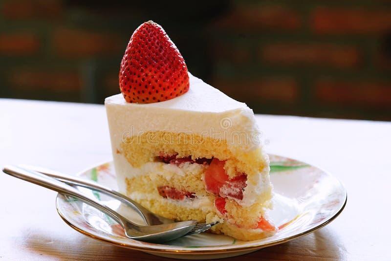 草莓脆饼冠上了用在与咖啡馆环境的木桌安置的在白色板材和一个大新鲜的草莓 图库摄影