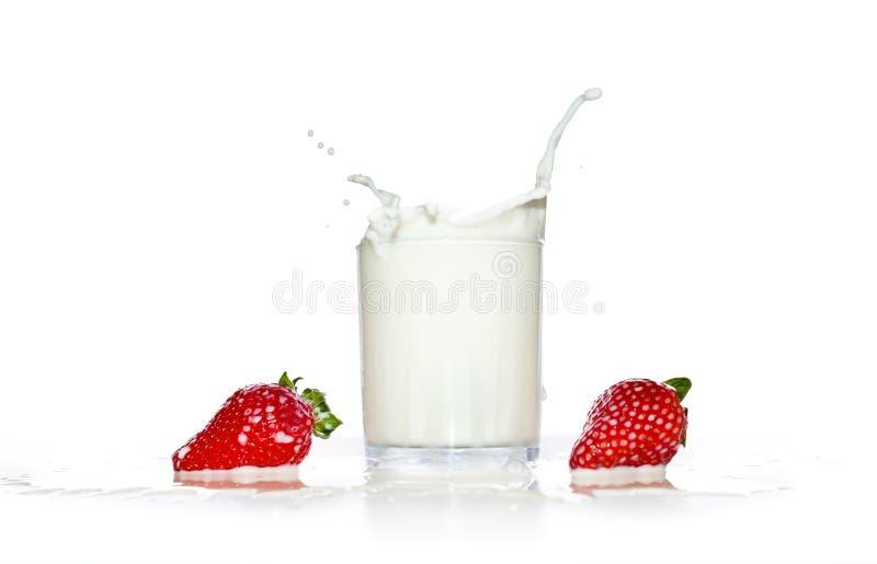 草莓落入一杯牛奶 库存图片