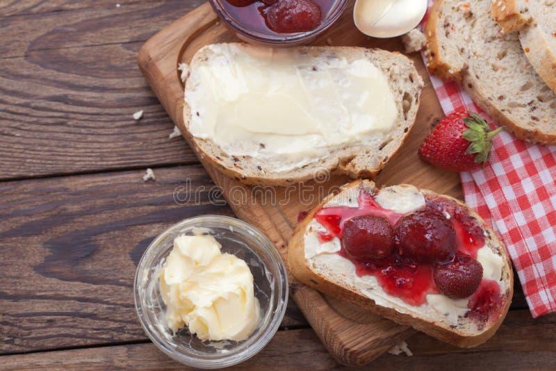 草莓酱、黄油和面包在木桌上 库存图片