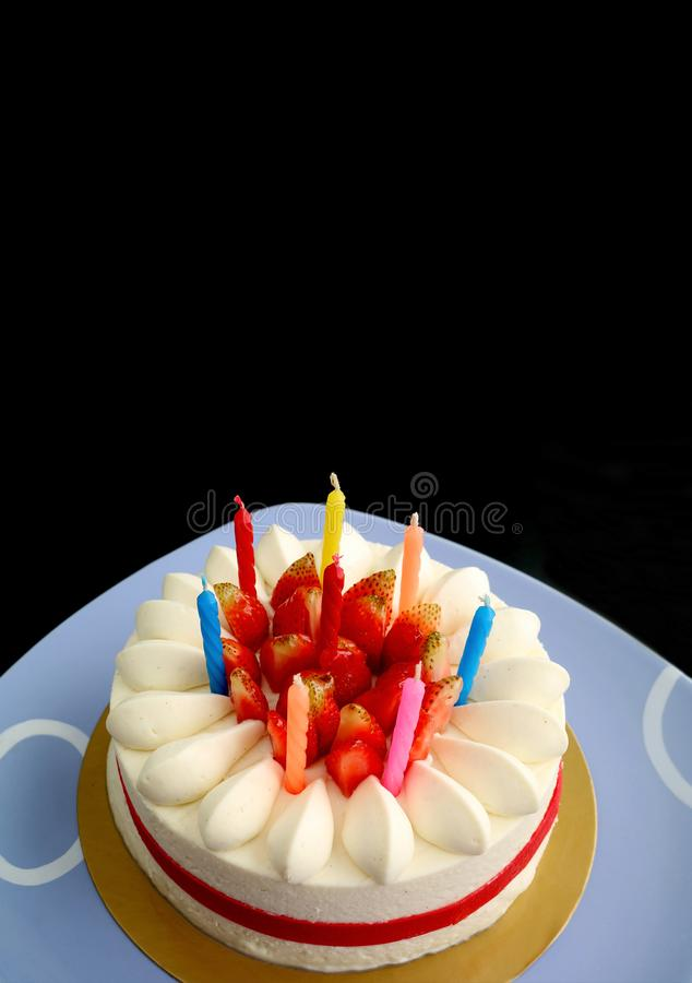 草莓香草与多色蜡烛的短小蛋糕的垂直的图象为在黑背景的庆祝做准备 库存照片