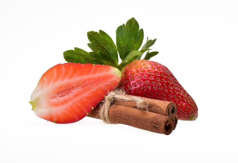草莓,整个和对分与绿色叶子和三根肉桂条 免版税图库摄影
