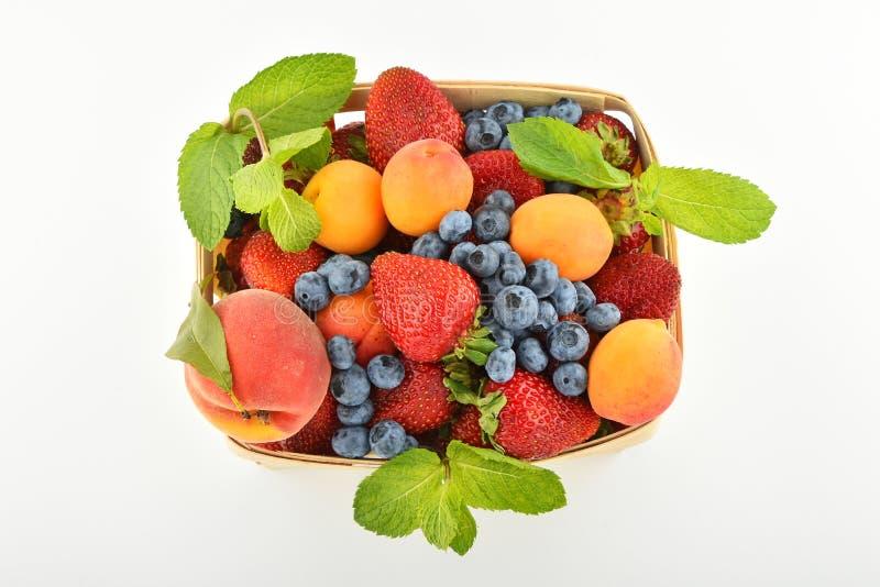 草莓,杏子,蓝莓,在被隔绝的篮子的桃子  库存照片