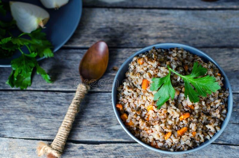 荞麦粥用红萝卜和荷兰芹在老木背景 免版税库存照片