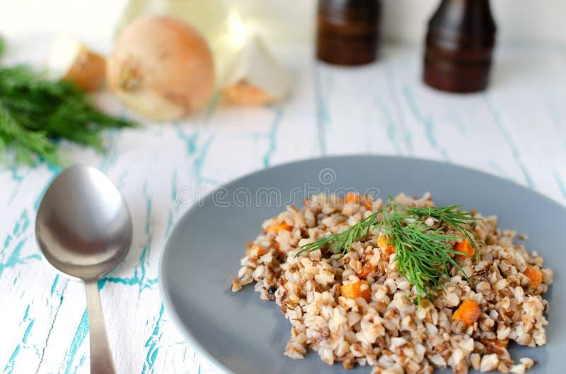荞麦粥用红萝卜和荷兰芹在蓝色板材 在金黄葱背景,绿色荷兰芹和盐和胡椒磨 图库摄影