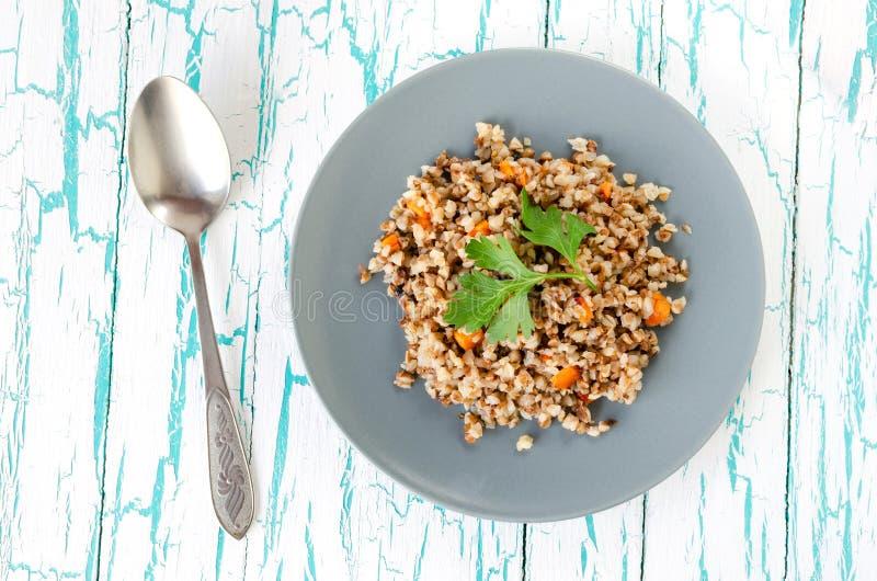 荞麦粥用红萝卜和荷兰芹在轻的背景在一块灰色板材 库存图片
