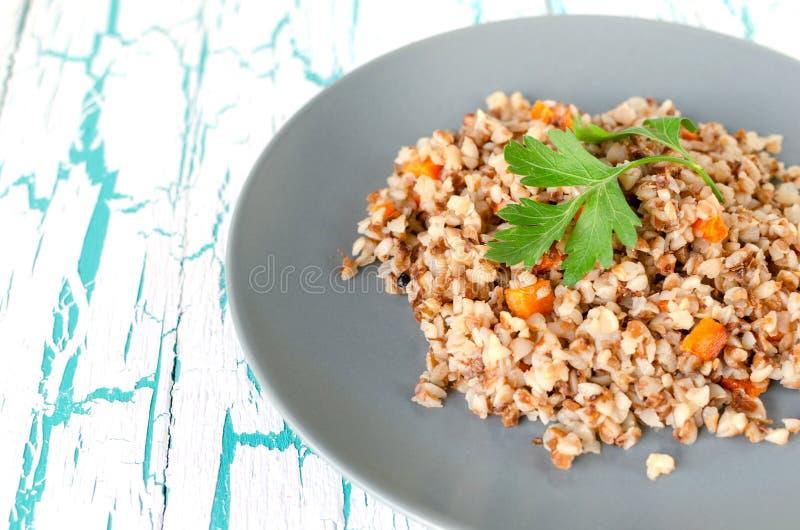 荞麦粥用红萝卜和荷兰芹在轻的背景在一块灰色板材 免版税库存图片
