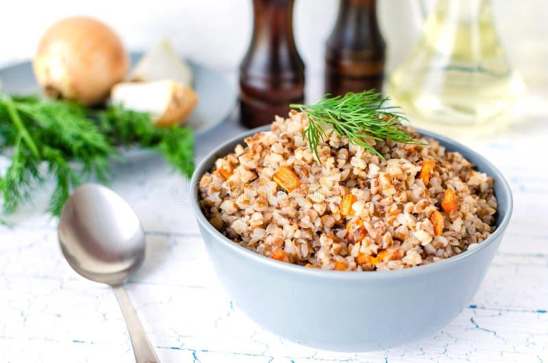 荞麦粥用红萝卜和莳萝在一块蓝色板材 在金黄葱背景,绿色莳萝和盐和胡椒磨 免版税库存图片
