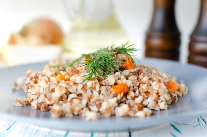 荞麦粥用红萝卜和莳萝在一块蓝色板材 在金黄葱背景,绿色莳萝和盐和胡椒磨 库存图片
