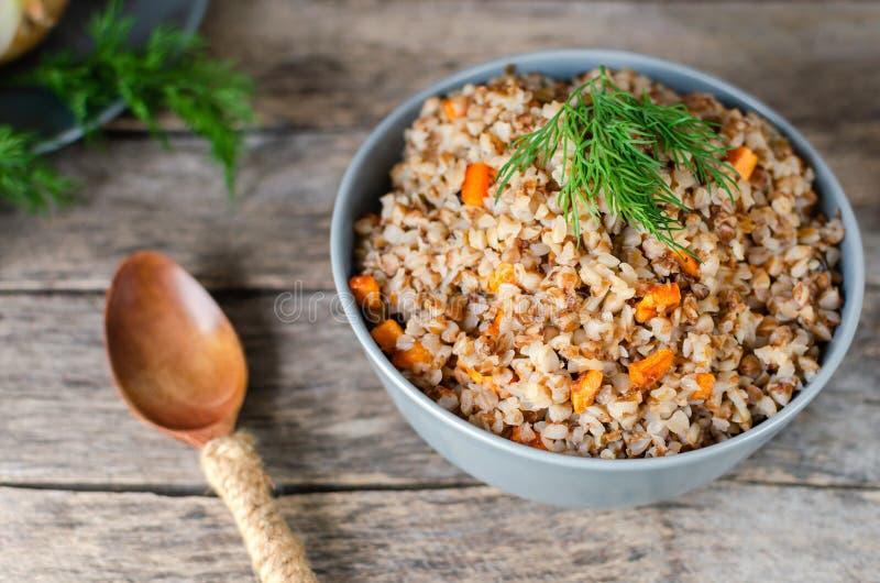 荞麦粥用红萝卜和莳萝在老木背景 库存照片