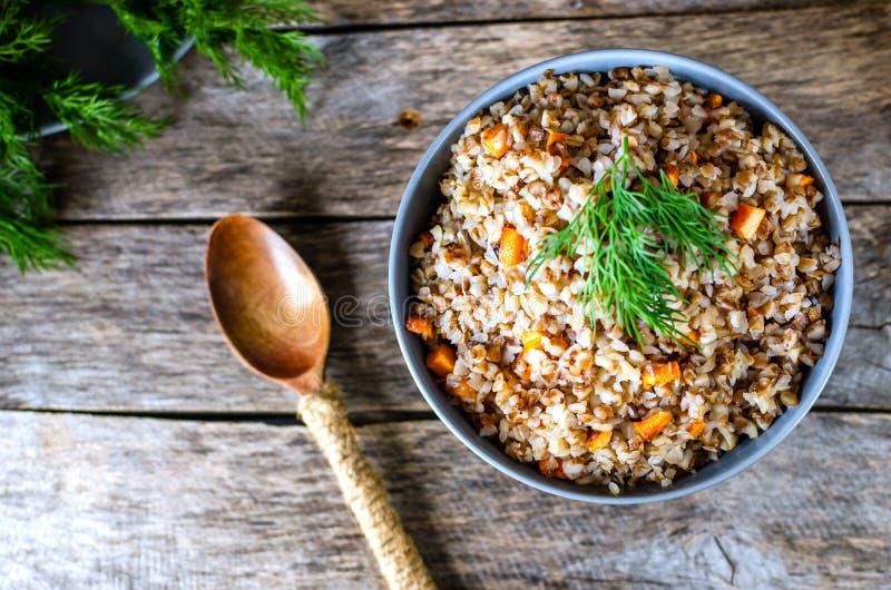 荞麦粥用红萝卜和莳萝在老木背景 免版税库存图片
