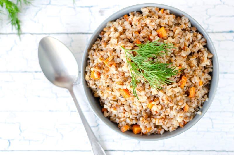 荞麦粥用红萝卜和莳萝,在轻的背景的顶视图 免版税库存图片