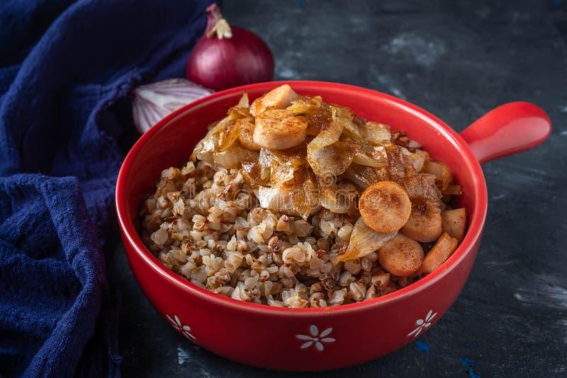 荞麦粥用香肠和油煎的葱在一个红色平底锅在黑暗的背景,拷贝空间 库存照片