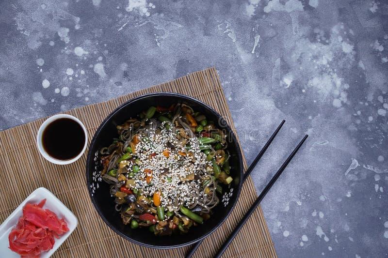 荞麦面条用肉和菜,在灰色的亚洲铁锅 免版税图库摄影