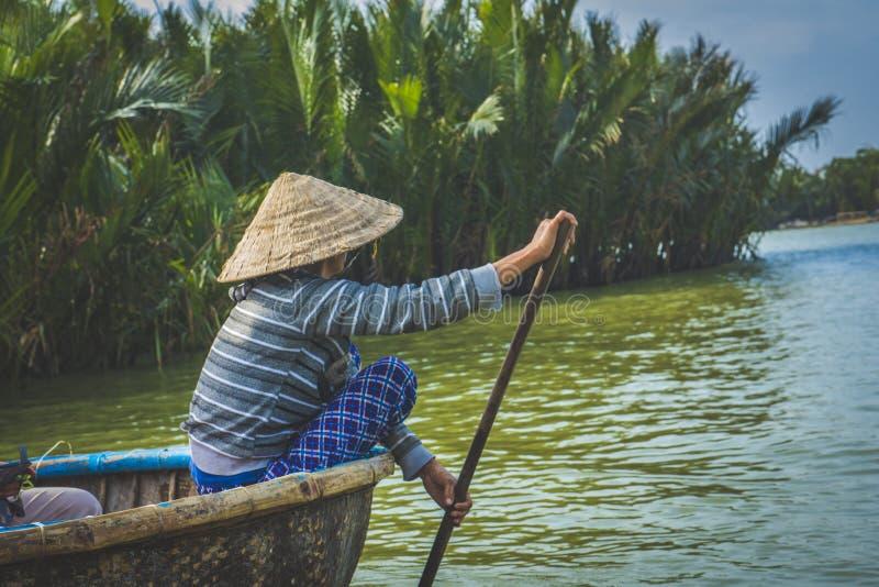 荡桨一条篮子小船,沿椰子水森林的妇女,在会安市 免版税库存照片