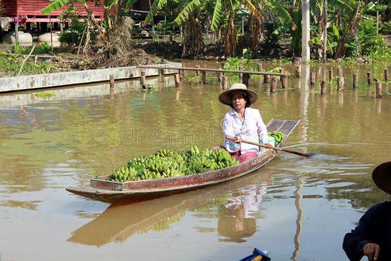 荡桨与许多的妇女未加工的香蕉 免版税库存图片