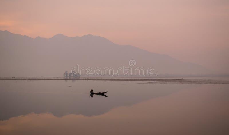 荡桨他的在平安的日出的人小船 免版税图库摄影