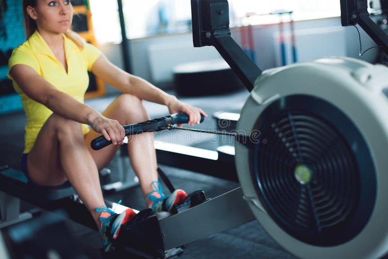 荡桨在健身房 使用划船器的少妇训练 库存照片