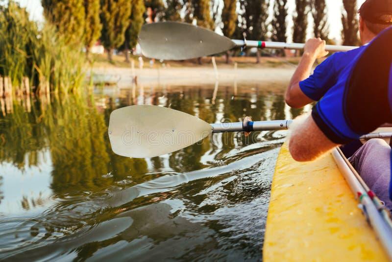 荡桨在河的年轻人皮船在日落 结合朋友获得乘独木舟的乐趣在夏天 桨特写镜头  免版税图库摄影