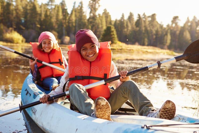 荡桨在湖的两个孩子皮船 图库摄影