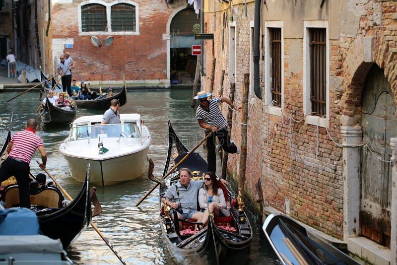 荡桨在狭窄的街道之间的长平底船 免版税库存照片