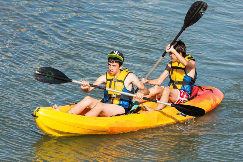 荡桨在皮船的孩子 免版税库存图片