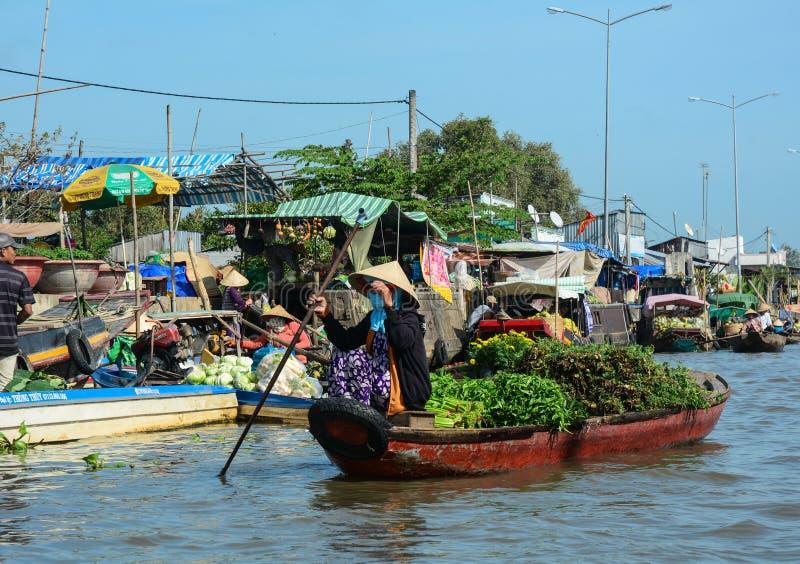 荡桨小船的妇女在浮动市场上在芹苴市,越南 库存图片