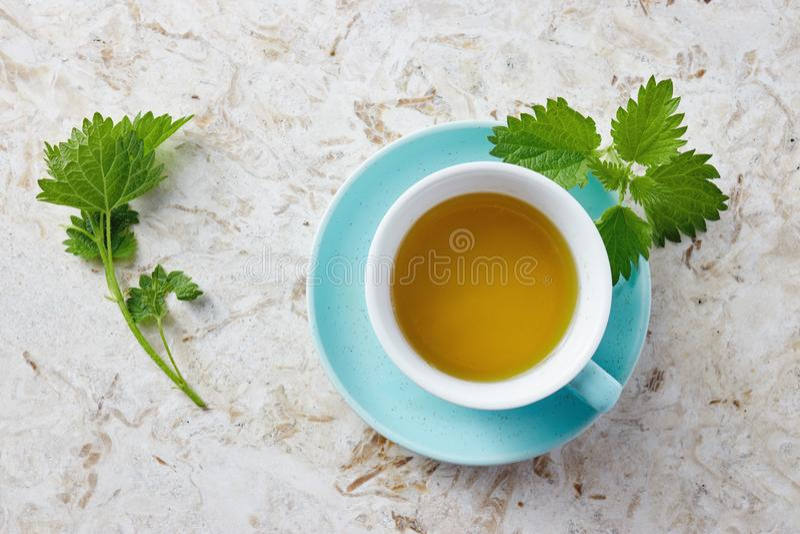 荨麻茶和新鲜的荨麻叶子 库存图片