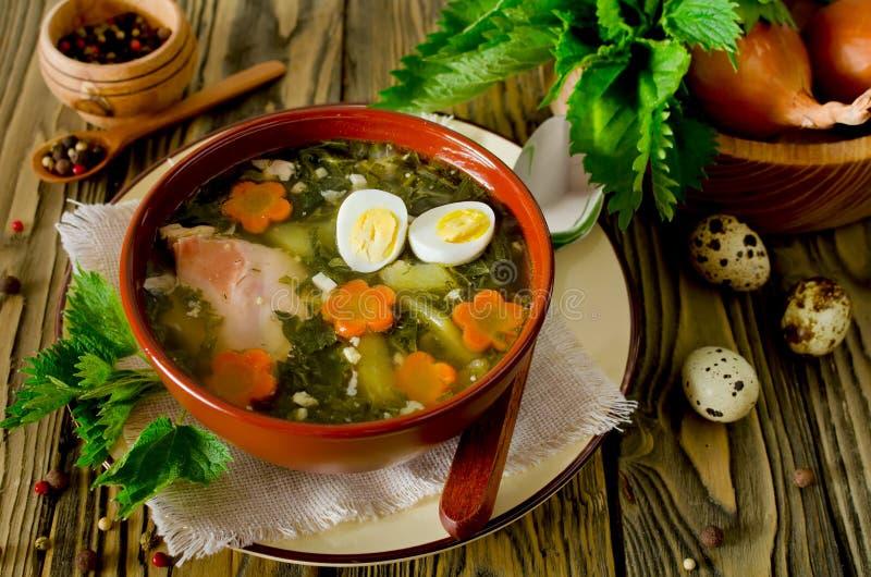 荨麻汤用鸡蛋和红萝卜在碗在桌上 免版税库存照片