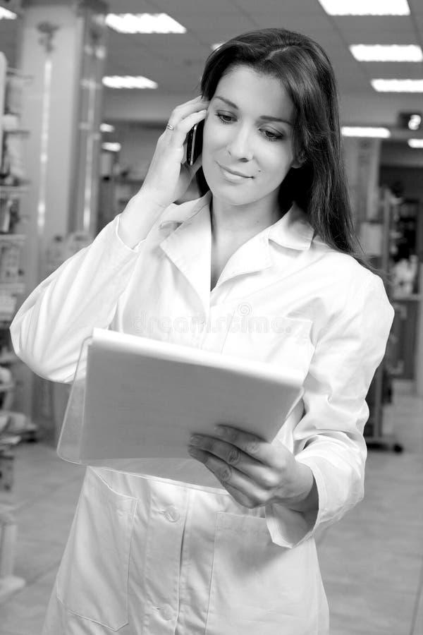 药剂师妇女谈话与电话的顾客 库存图片
