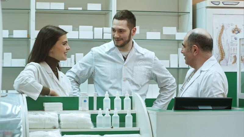 药剂师站立在药房药房和谈的正面的化学家妇女和人队  免版税库存照片