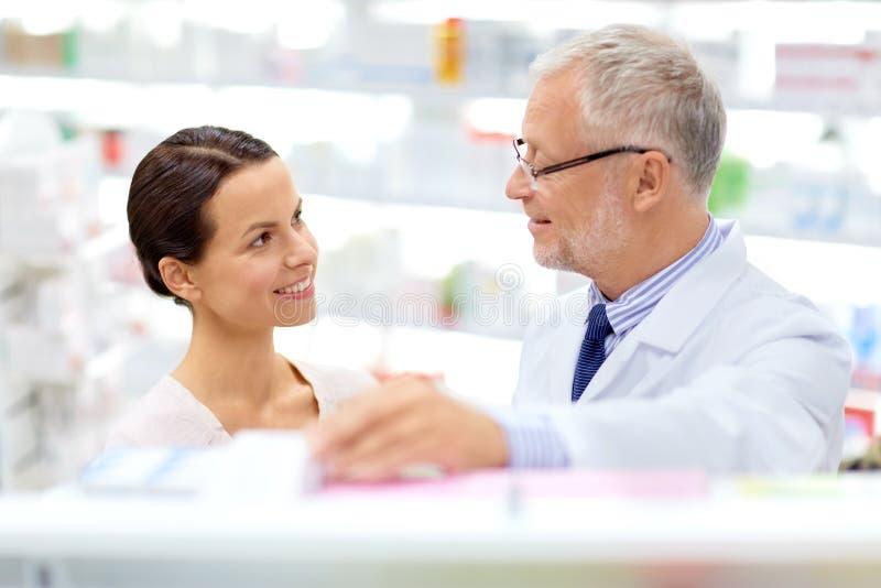 药商和妇女有药物的在药房 免版税图库摄影