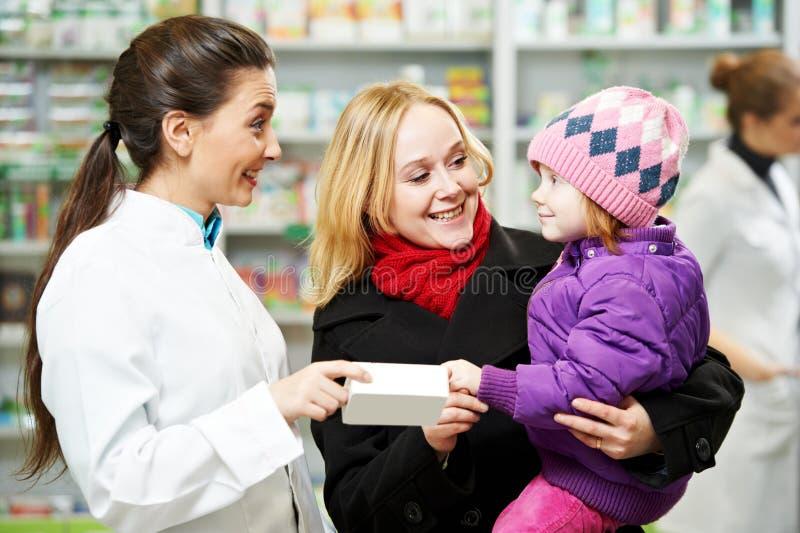药房化学家、母亲和孩子在药房 图库摄影