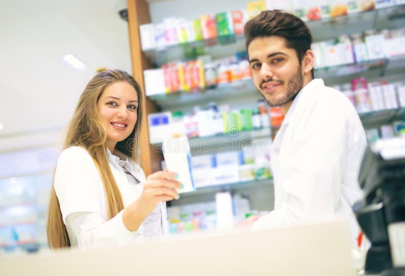 药房的女性和男性药剂师 库存照片