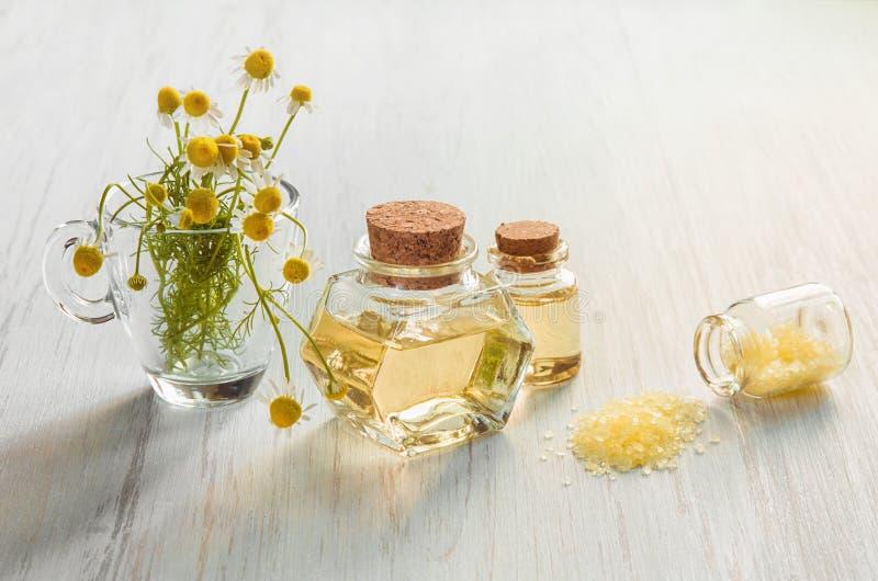药房黄色春黄菊花和医药注入在玻璃瓶和温泉盐在木轻的背景 免版税库存照片