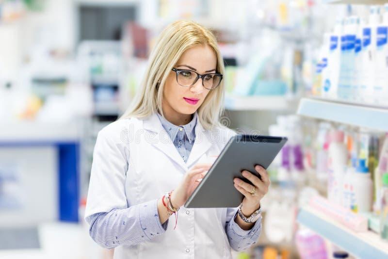 药房细节-白色制服的在配药或医疗领域的医生使用片剂和技术 库存图片