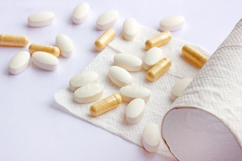 药片、胶囊和片剂有手纸的在轻的背景 药房和医学腹泻和便秘概念的 库存照片