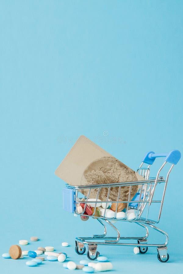 药片和信用卡在购物的台车在蓝色背景 医疗保健费用的,药房,保险创造性的想法和 库存图片