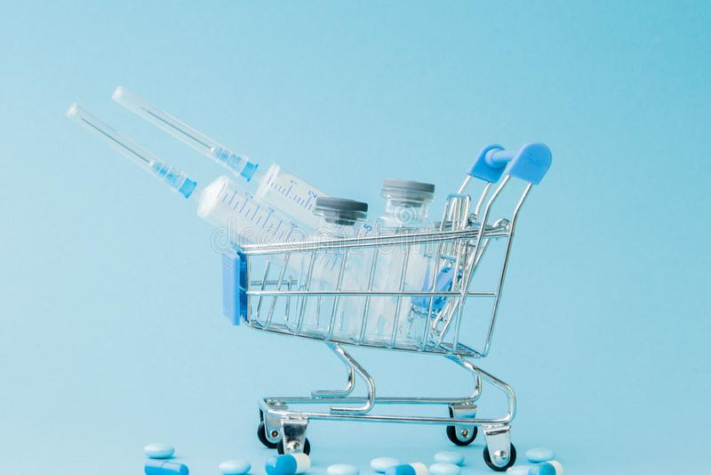 药片和医疗射入在购物的台车在蓝色背景 医疗保健费用的,药房创造性的想法 库存照片