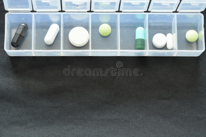 药片和胶囊在塑料盒在黑织品 库存图片