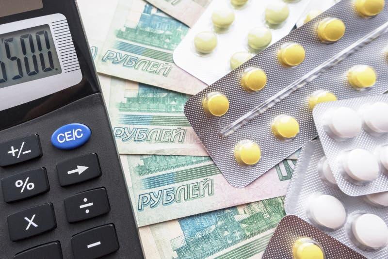 药片和计算器在俄罗斯卢布背景  免版税库存图片