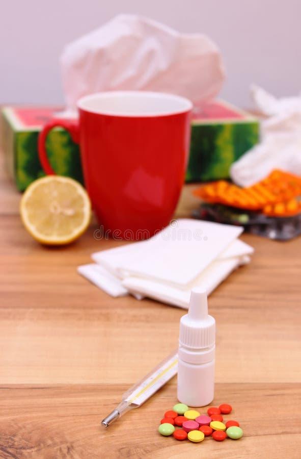 药片和滴鼻剂寒冷、使用的手帕和热的茶的用柠檬 免版税库存照片