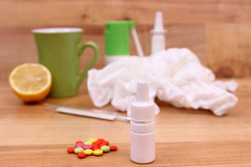 药片和滴鼻剂寒冷、使用的手帕和热的茶的用柠檬 免版税图库摄影