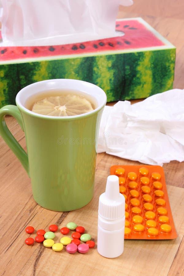 药片和滴鼻剂寒冷、手帕和热的茶的用柠檬 图库摄影