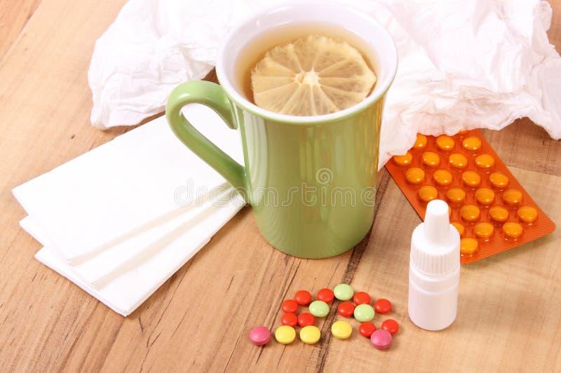 药片和滴鼻剂寒冷、手帕和热的茶的用柠檬 免版税图库摄影